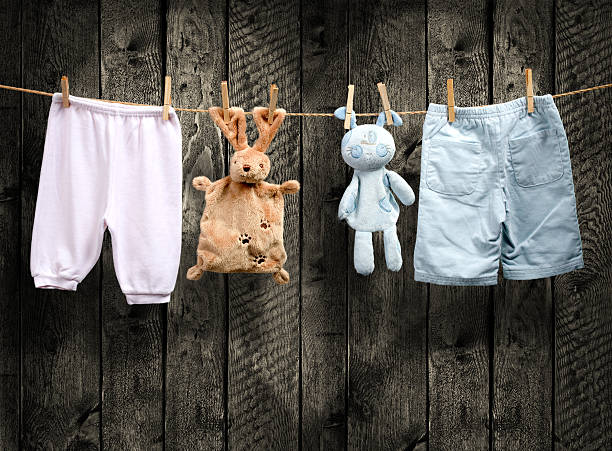 Is the baby a boy or a girl? Clothing and toys on a rope stock photo