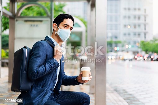 Businessman sitting alone and working on his laptop while waiting for a bus with pollution mask