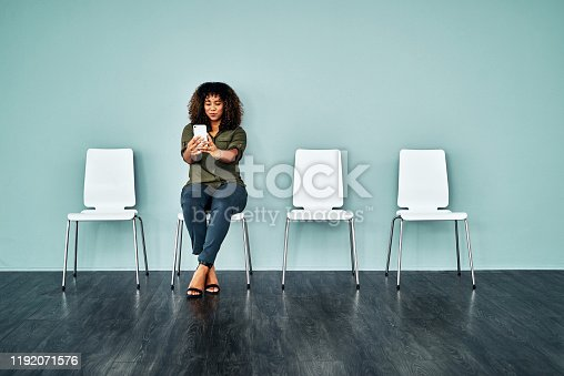 Studio shot of a young businesswoman using a smartphone while waiting in line against a blue background