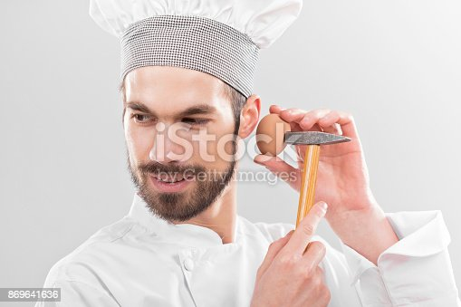 Kitchen chef holding hammer and egg