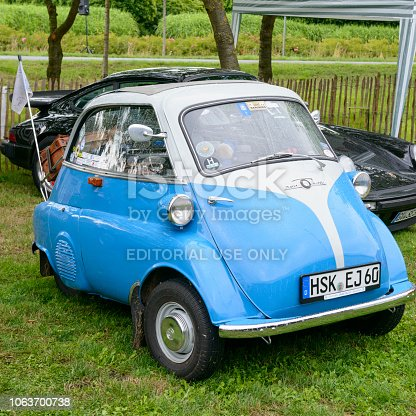 BMW Isetta 250 1950s microcar or bubble car. The car is on display during the 2017 Classic Days event at Schloss Dyck. People in the background are looking at the cars.
