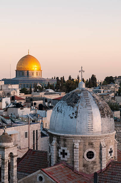 Islam and Christianity in Jerusalem Old City Rooftops of two faiths in Jerusalem: A cross on a church dome and a crescent atop the Dome of the Rock muslim quarter stock pictures, royalty-free photos & images