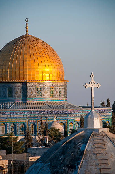 Islam and Christianity Rooftops of two faiths in Jerusalem: A cross on a church and a crescent atop the Dome of the Rock dome of the rock stock pictures, royalty-free photos & images