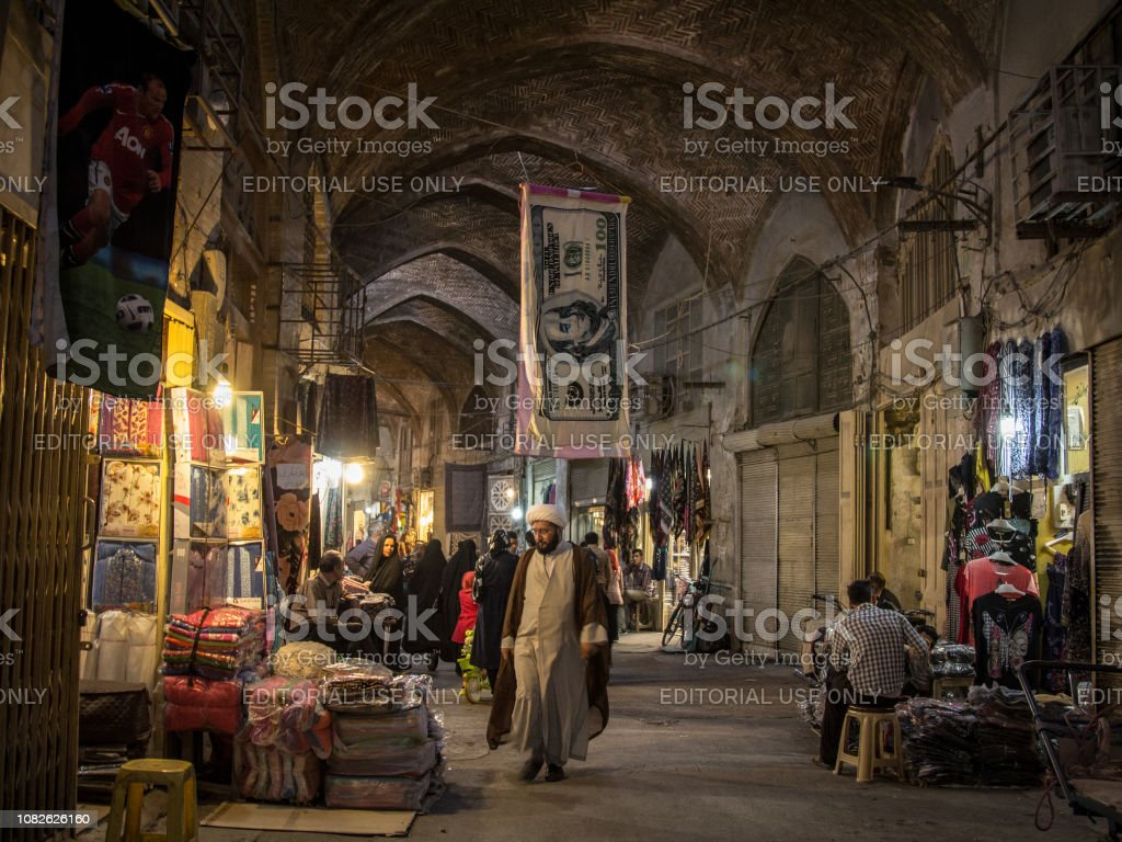 Islam passing under a towel shaped like a US Dollar bill in the Isfahan bazar in the evening. The iranian rial, iran currency, is being devaluated facing the dollar stock photo