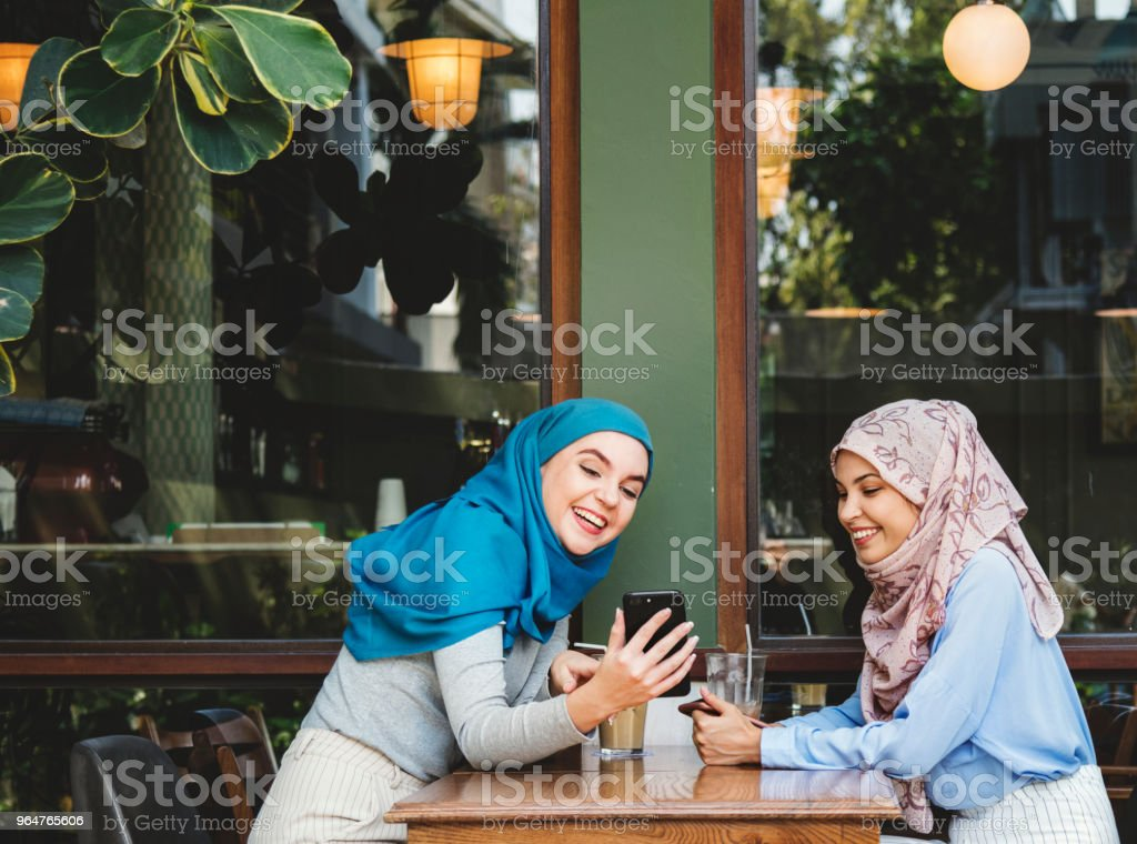 Islamic friends talking and looking on the smart phone royalty-free stock photo