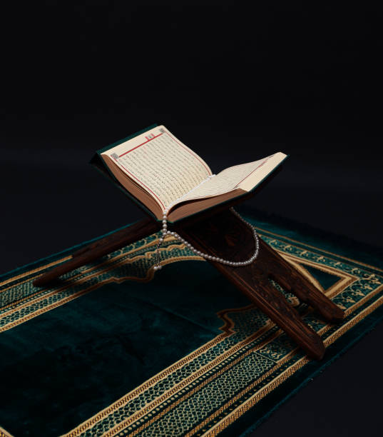 islamic holy book quran on wood carving rahle with rosary beads and prayer rug on black background. kuran the holy book of muslims. ramadan concept. - cora��o imagens e fotografias de stock