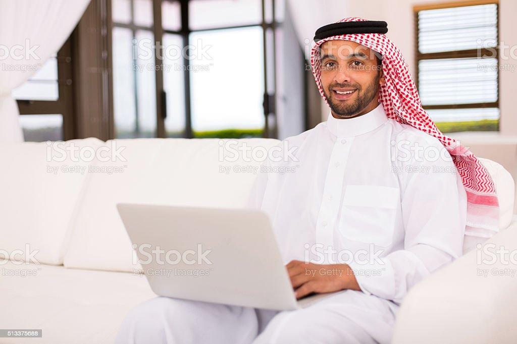 islamic man using laptop stock photo