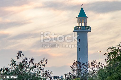 Telephoto shot of a Qatari mosque minaret above the trees after sunset - Doha, Qatar