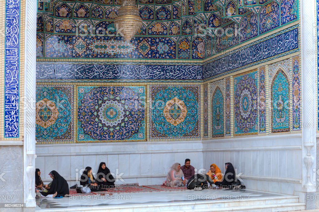 Islamic pilgrims group resting in outer recess of mosque, Iran. stock photo