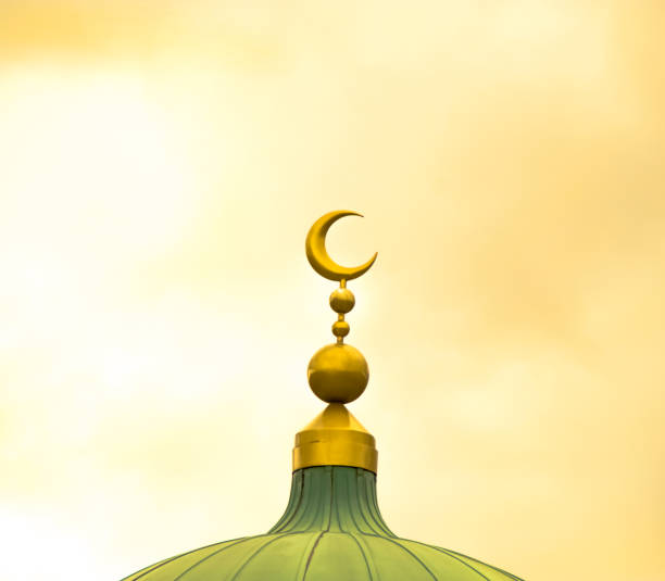 Islamic symbol on mosque's cupola on yellow cloudy background Islamic symbol on mosque's cupola on yellow cloudy background muslim quarter stock pictures, royalty-free photos & images