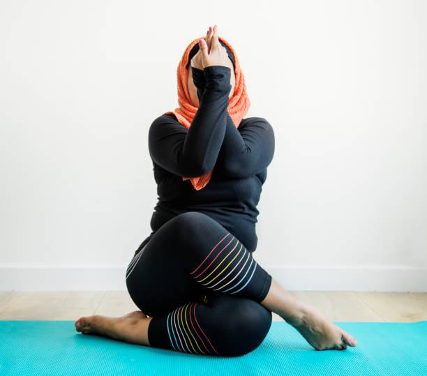 islamic woman doing yoga in the room - скромная одежда стоковые фото и изображения