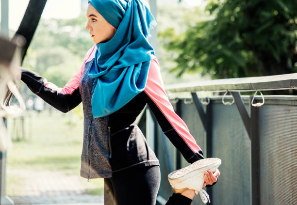 islamic woman stretching after workout at the park - hijab foto e immagini stock