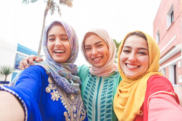 islamic young friends taking selfie with smartphone camera outdoor - happy arabian girls having fun with new trend technology - friendship and millennial app concept - focus on faces - algeria stock photos and pictures