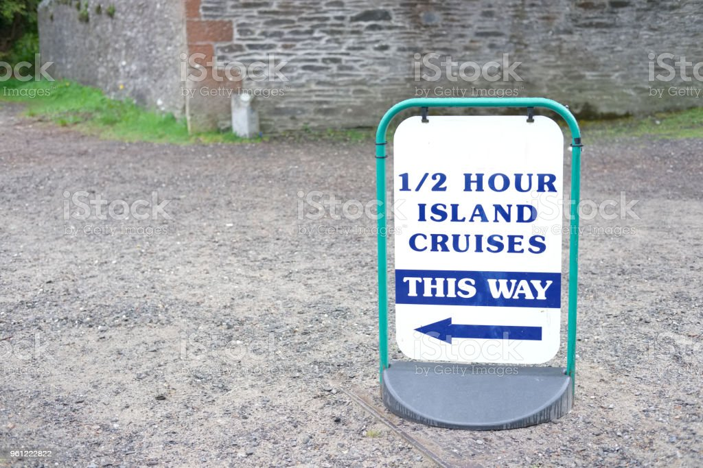 island cruises this way sign tourists travellers boat trip direction stock photo