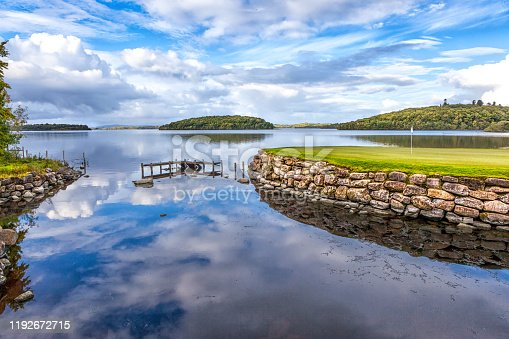 Stunning image of Island Green surrounded by Lake on a world class golf course. The image also has the sky beautifully reflected in the mirror like water.