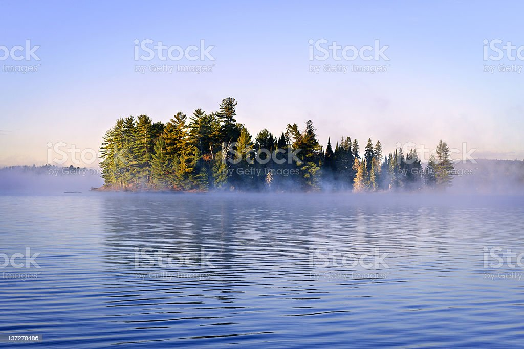 Island in lake with morning fog stock photo