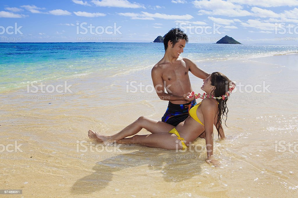 island man gives flower lei to a young woman royalty-free stock photo