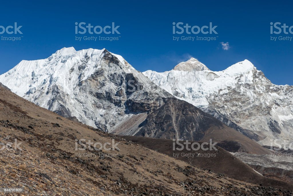 Island Peak or Imja Tse and Makalu view on the way to Everest Base Camp in Sagarmatha National Park, Himalayas, Nepal. Mountain summits in snow under the blue sky. Summits of Himalayan mountains. stock photo