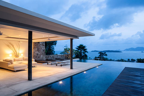 Island Villa Luxury Island Home With Infinity Pool At Dusk. holiday villa stock pictures, royalty-free photos & images