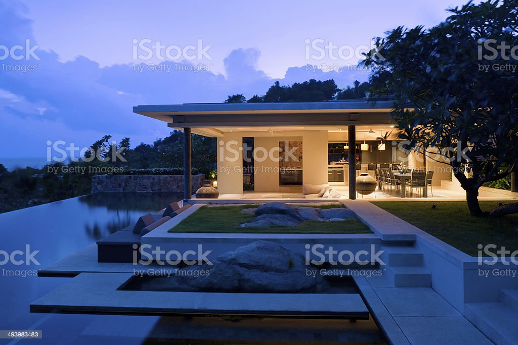 Island villa vacation home with swimming pool Vacation Home With Swimming Pool At Sunrise.  Architecture Stock Photo