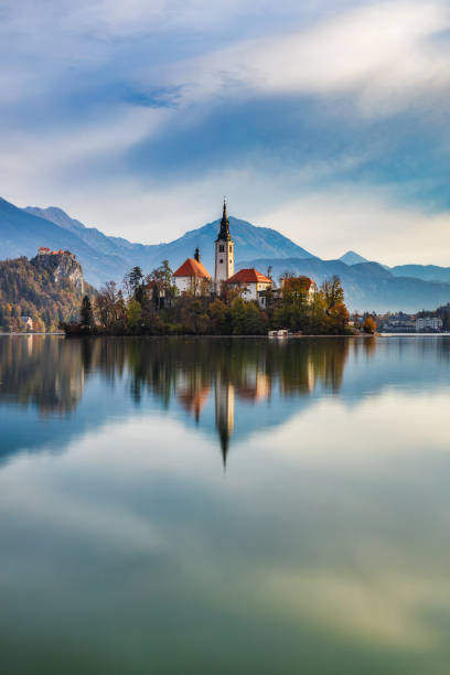Island with a church and reflection in calm water of lake Bled stock photo
