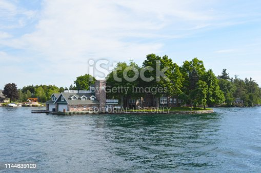 St Lawrence River's Thousand Islands, Canada and United States of America- June 19, 2016: Island with house, cottage in Thousand Islands Region in sunny summer day in Kingston, Ontario, Canada. 1000 Islands. Famous Canadian tourist vacation routes.