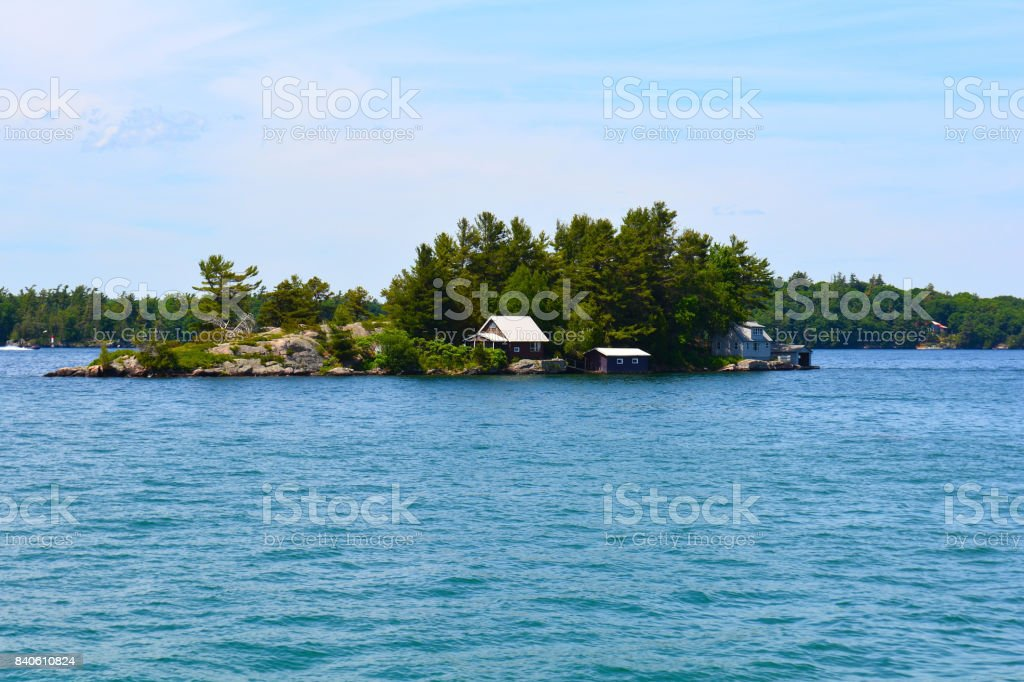 Island with house, cottage or villa in Thousand Islands Region in sunny summer day in Kingston, Ontario, Canada. 1000 Islands near Gananoque, ON. Famous Canadian tourist vacation routs. stock photo