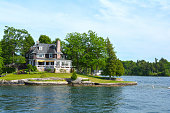 St Lawrence River's Thousand Islands, Canada and United States of America- June 19, 2016- Island with house, cottage or villa in Thousand Islands Region in sunny summer day in Kingston, Ontario, Canada. 1000 Islands near Gananoque, ON. Canadian vacation