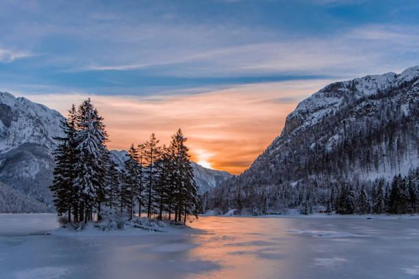 Insel mit Bäumen im Winter zugefroren See Predil und Sonnenuntergang – Foto