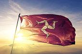 Isle of Mann Manx flag on flagpole textile cloth fabric waving on the top sunrise mist fog