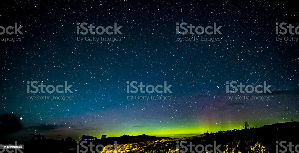 Isle of Skye Northern Lights and stars Looking northwards in the Isle of Skye Scotland to the beautiful colors of the night sky showing thousands of stars, satellites and the Northern Lights, Aurora Borealis. Big Dipper or Plough constellation in the center while the brightest star in the bottom left is Arcturus. Astronomy Stock Photo