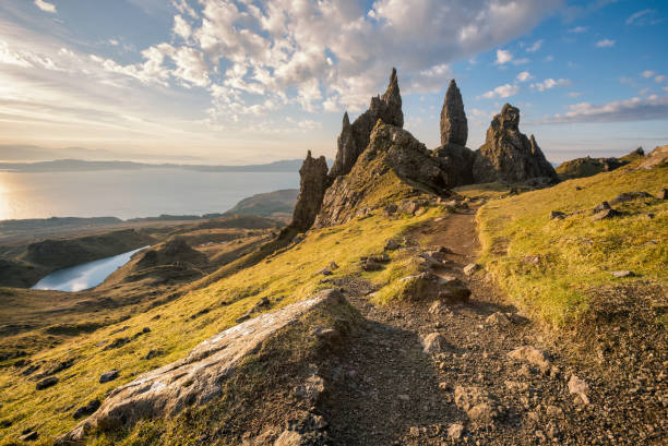 Isle of Skye, Scotland. The Old Man of Storr at sunrise Sunrise at the Old Man of Storr, Isle of Skye, Scotland. Close look at the massive pinnacle of the Old Man of Storr - one of Scotland's most iconic places. The Old Man is in fact just one element in an array of fantastic rock features, and the views out over the Sound of Raasay and to the mainland are stunning. The Storr (Scottish Gaelic: An Stòr) is a rocky hill on the Trotternish peninsula of the Isle of Skye in Scotland. The hill presents a steep rocky eastern face overlooking the Sound of Raasay, contrasting with gentler grassy slopes to the west. isle of skye stock pictures, royalty-free photos & images