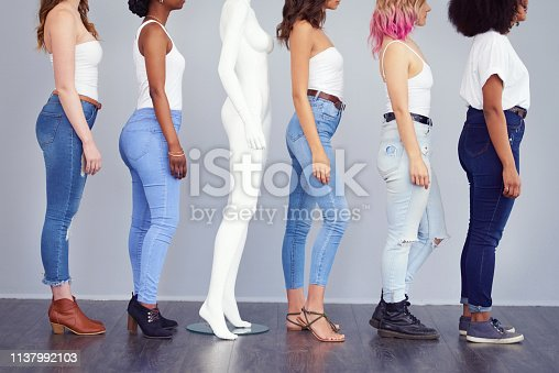 Studio shot of a group of attractive young women posing with a mannequin against a gray background