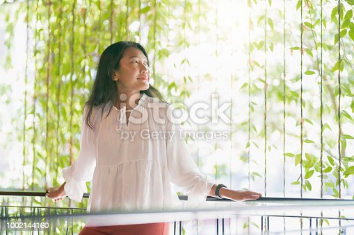 Beautiful, young Malaysian woman leaning on the balcony fence and enjoying.