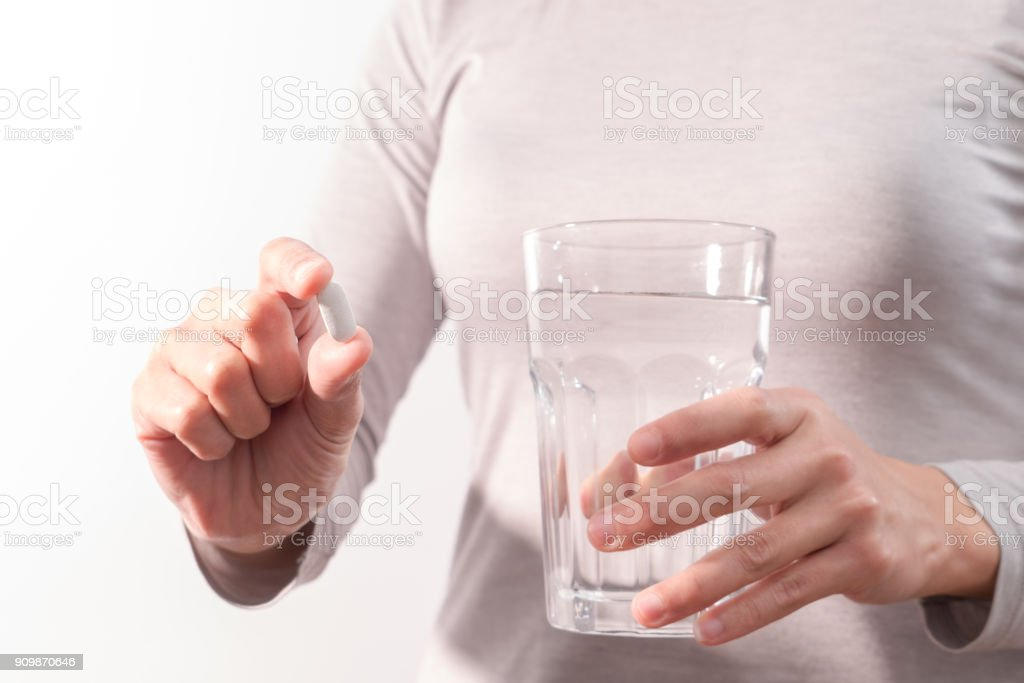 isolate of the women hand holding the medicine with a glass of water,...