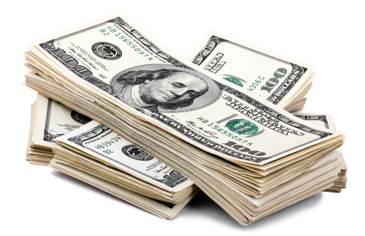 Three stacks of 100 US$ money notes on top of eachother, isolated on white background.