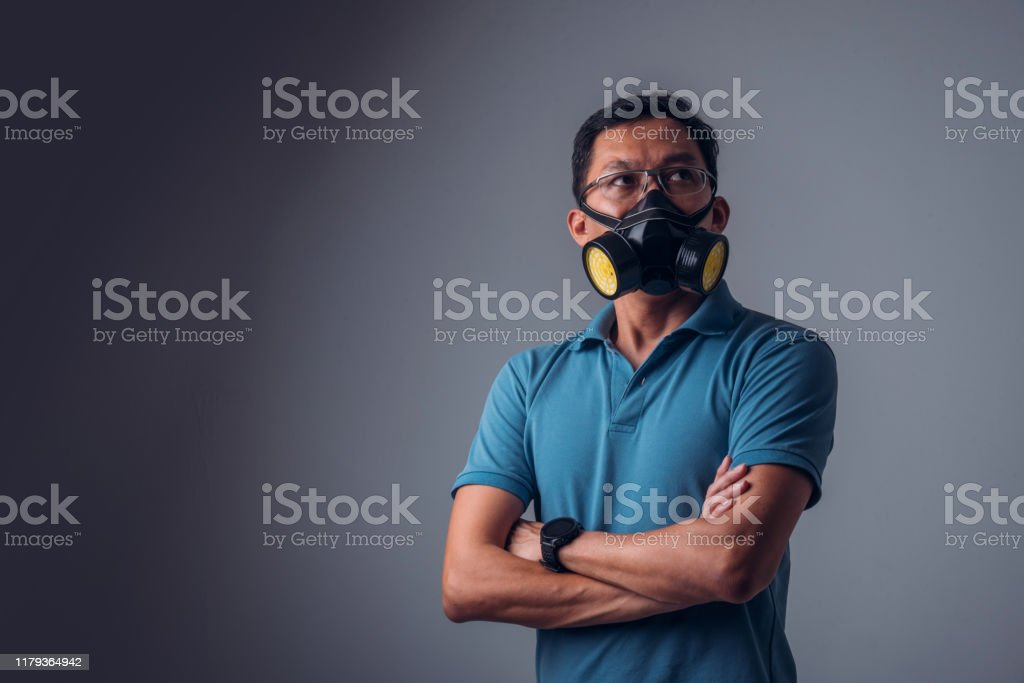 Isolated Asian Man Wearing Gas Mask with dark color background Portrait of Asian Man in a casual attire and wearing Gas Mask, looking to his front with dark color background Adult Stock Photo