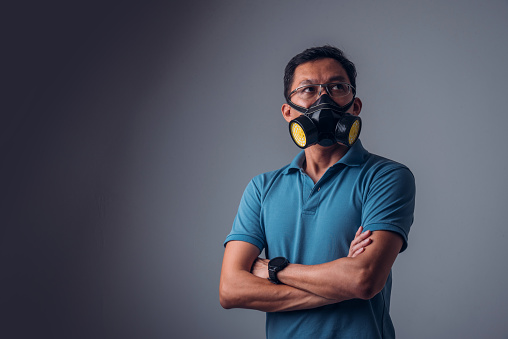 Isolated Asian Man Wearing Gas Mask With Dark Color Background Stock Photo - Download Image Now