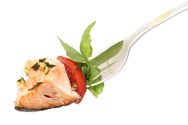 Isolated background of salmon, rucola and tomato on fork stock photo