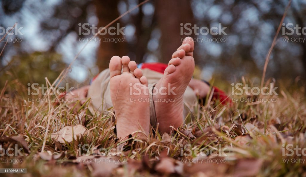 Isolated bare legs of a lying human being stock photo