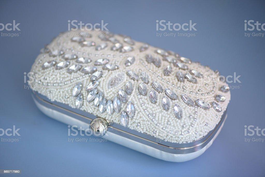 Granos aislados y adornado de diamantes de imitación embrague, en un paño de cuero de gamuza azul - foto de stock