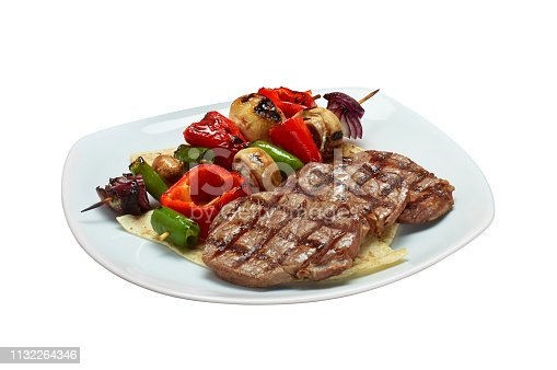 Isolated Beef Steaks with Vegetable Skewers in a White Plate