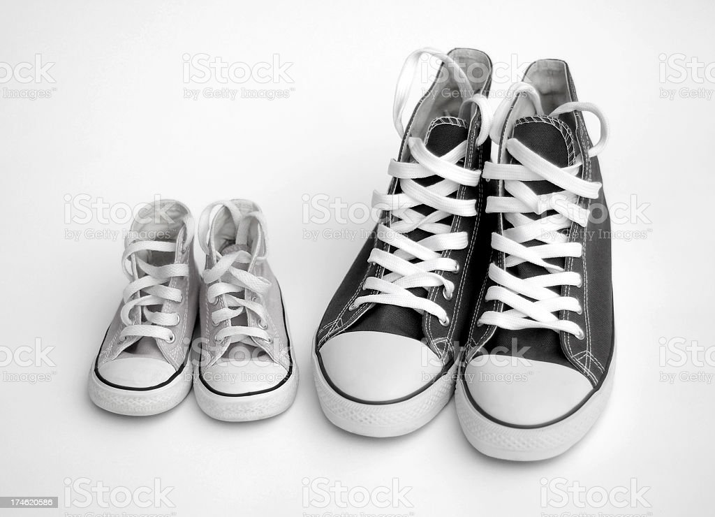 Isolated black and white images of adult and child sneakers stock photo