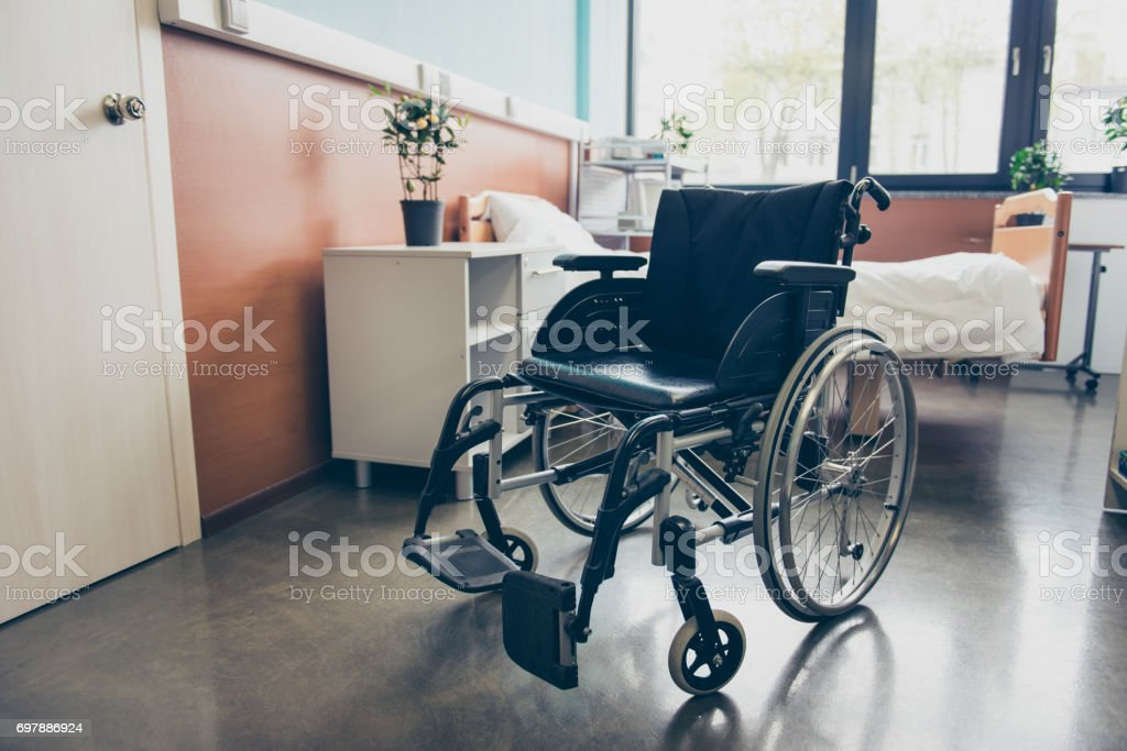 Isolated black wheel chair in the empty ward of the hospital stock photo