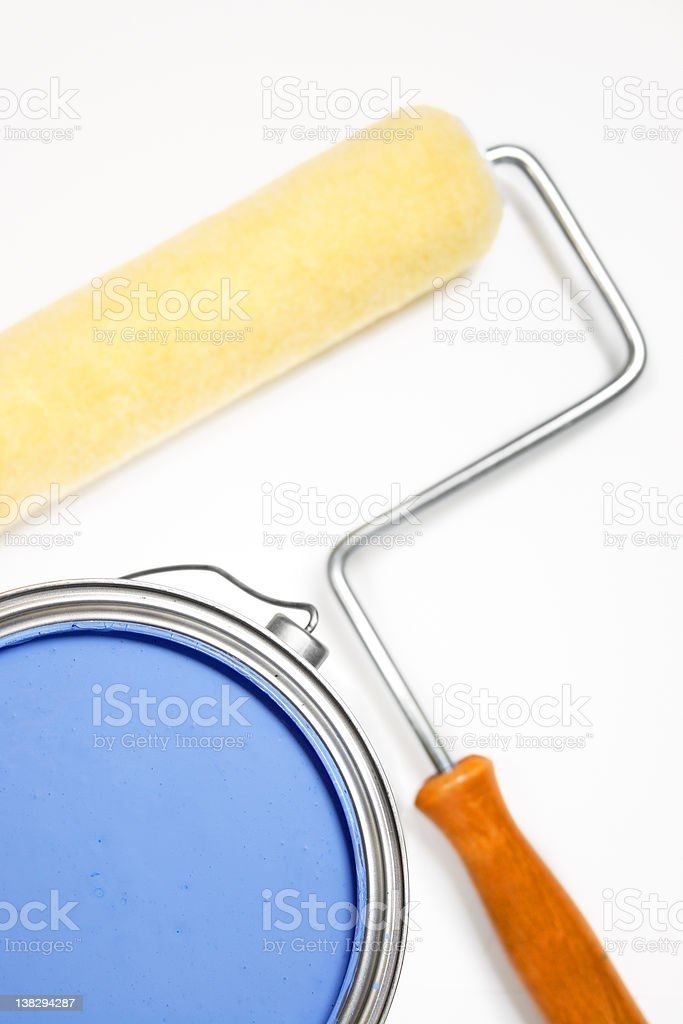 isolated blue can of paint with roller in background royalty-free stock photo