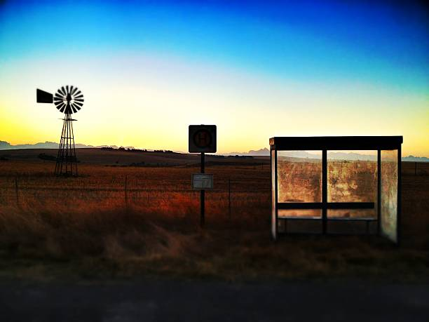 Isolated Bus Stop with Windmill in Background.