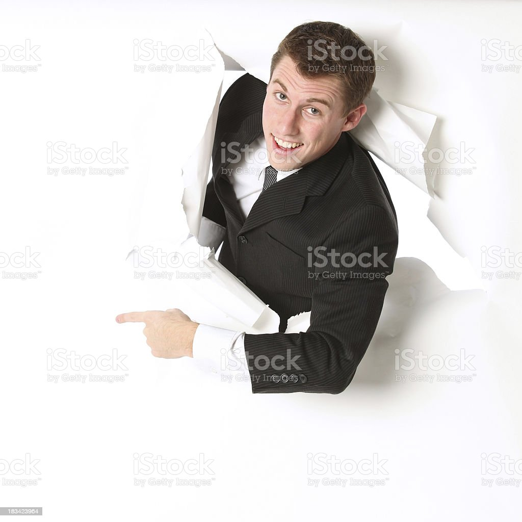 Isolated businessman emerging through a hole and pointing stock photo