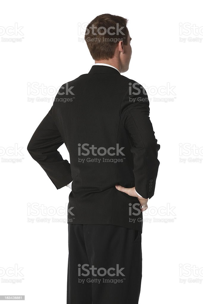 Isolated businessman hands on hips facing away stock photo