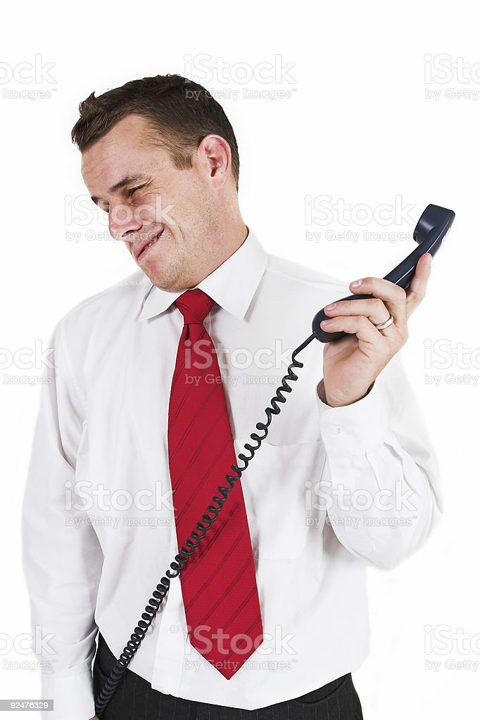 Isolated businessman pulling face away from telephone royalty-free stock photo