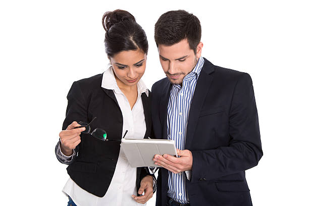 Isolated businesswoman and businessman looking at tablet pc. stock photo
